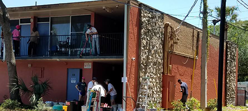 Orlando volunteers help to paint Maxwell Garden, affordable low-income efficiency apartments for former chronically homeless men and women